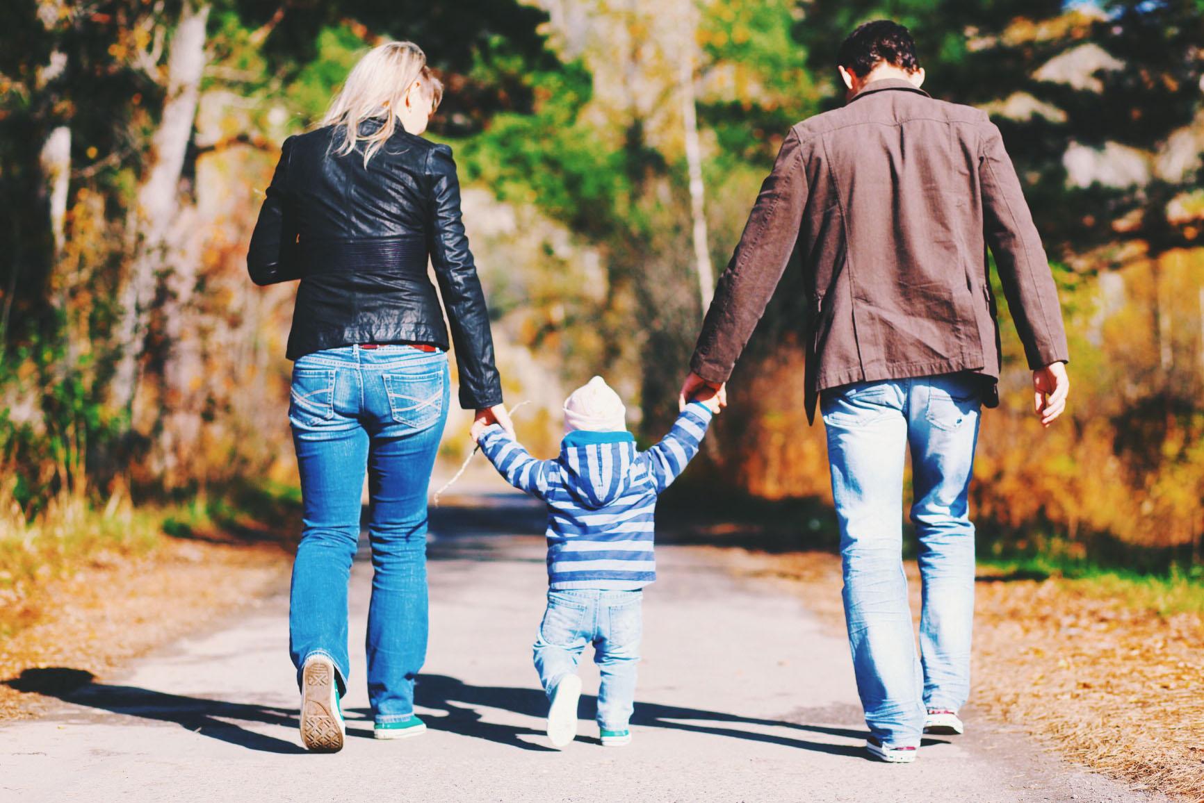 eine Familie beim Händehalten während eines Spaziergangs